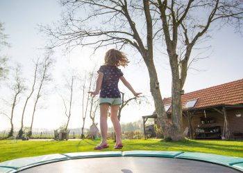 Young girl bouncing on a trampoline in the yard