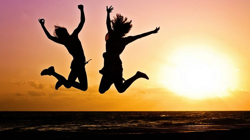 Two youths jumping with sun in background