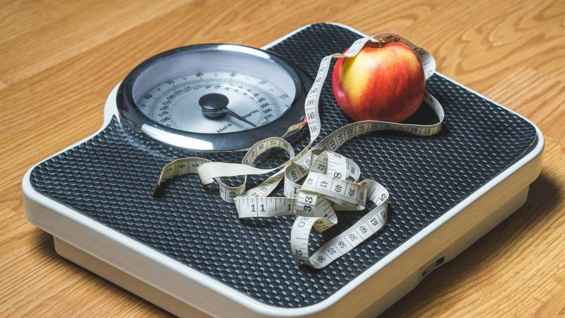 Weight scale with measuring tape and apple on top