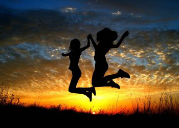 Two children jumping with sun setting