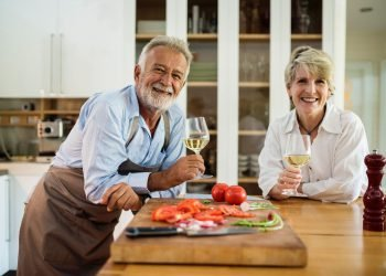 Senior couple in kitchen drinking wine