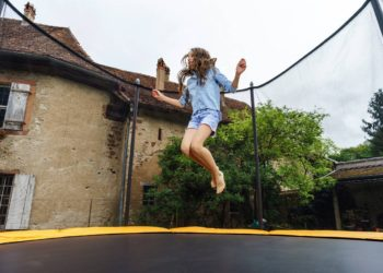 teenage girl jumping on trampoline
