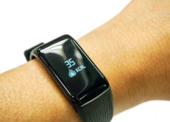 Closeup human's hand wear black healthy smart band with numbers and icon of calories burned display on screen isolate on white background.