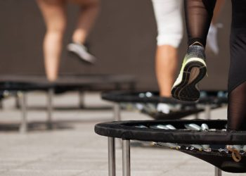 Feet on fitness trampolines in gym