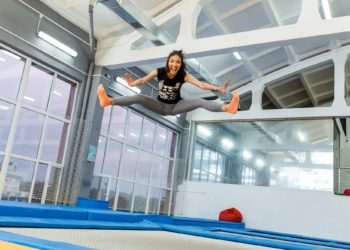 Twine jumping young woman on the trampoline