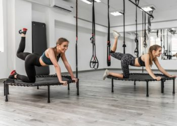 Two women jumping on trampoline, young fitness girls trains on a fitness studio.