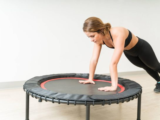 Confident young brunette woman exercising on mini trampoline during high intensity interval training