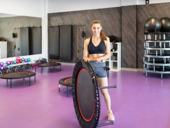 Smiling Caucasian woman in sportswear holding mini trampoline in gym