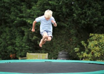 Boy jumping with head down on trampoline