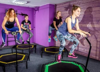 Women on exercise trampolines with stability bar