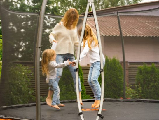 Family jumping on a trampoline with enclosure