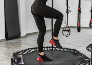 Fitness trainer in black leggins jump at the modern gym.