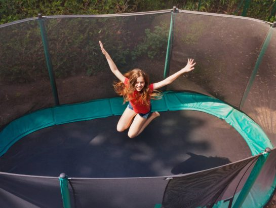 Above view portrait of happy teenage girl jumping on trampoline outdoors, holding her hands up