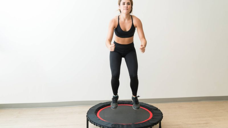 Beautiful slim female brunette rebounding during interval training at fitness studio