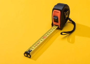 Measuring tape on yellow background