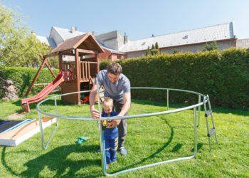 Father and son when installing large garden trampolines. Construction of private playground. The worker and his little helper.