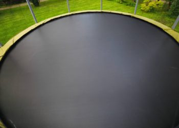 trampoline with big round mat on green lawn
