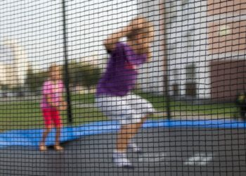 Defocused background of children on a trampoline. Grid in the foreground. Child Safety Concept