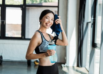 Woman wiping sweat and holding water bottle