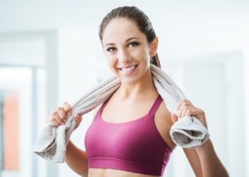 Beautiful sporty woman with towel relaxing at the gym after working out, healthy lifestyle and fitness concept