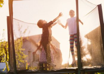 Cheerful happy kids having fun and jumping in a trampoline on a sunny day.