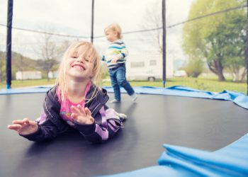 Beautiful little girl lying on the trampoline and posing