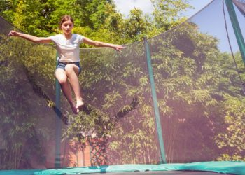 Portrait of teenage girl jumping on the trampoline with safety net in the backyard
