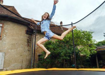 Cute teenage girl jumping on trampoline