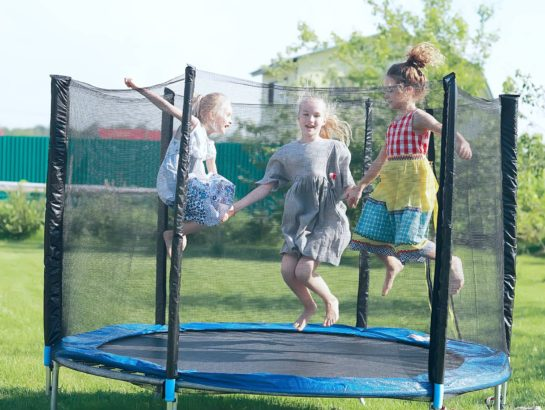 Three girls jumping on a small trampoline