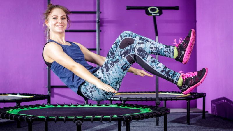 Woman in workout clothes bouncing on mini trampoline