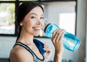 Woman drinking from water bottle after exercise