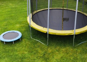 small trampoline near big one with round mat, size comparison, green lawn background