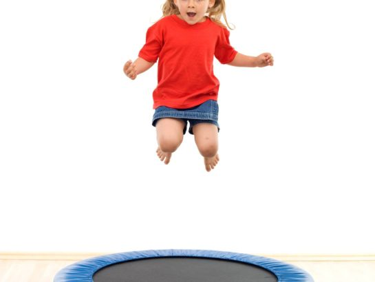 Little girl jumping on trampoline in gym - isolated, slight motion blur