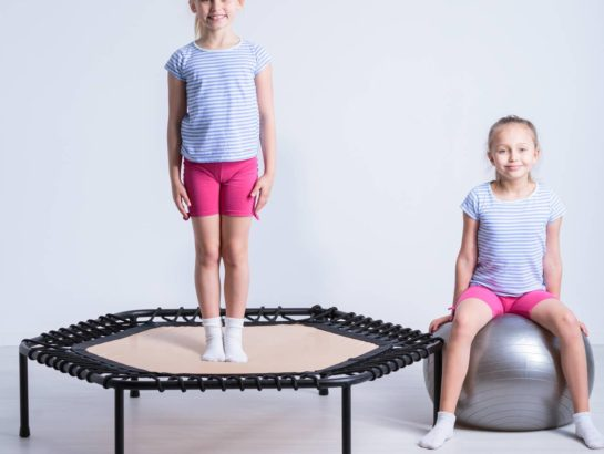 Shot of a girl standing on a trampoline and her friend sitting on a large exercise ball