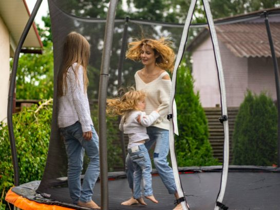 Mother and daughters on a trampoline and enclosure