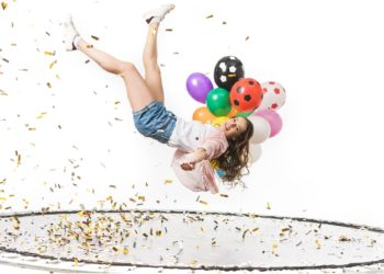 Girl on trampoline with balloons