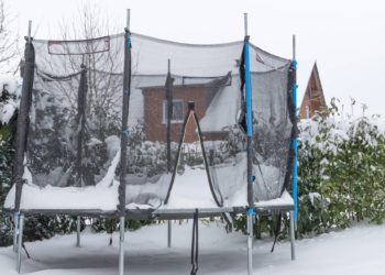 a big snow load on a weathered trampoline in wintertime