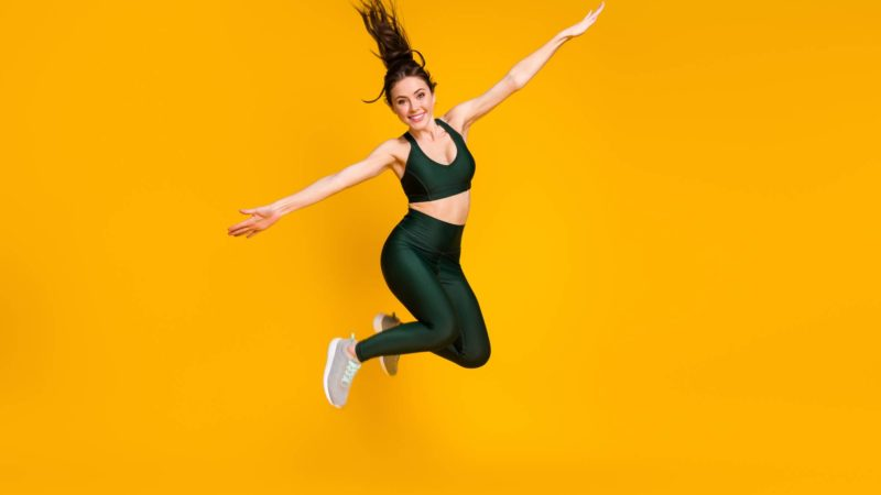 Full length photo of sportive excited lady jump high up spread hands wear sports suit sneakers isolated yellow color background